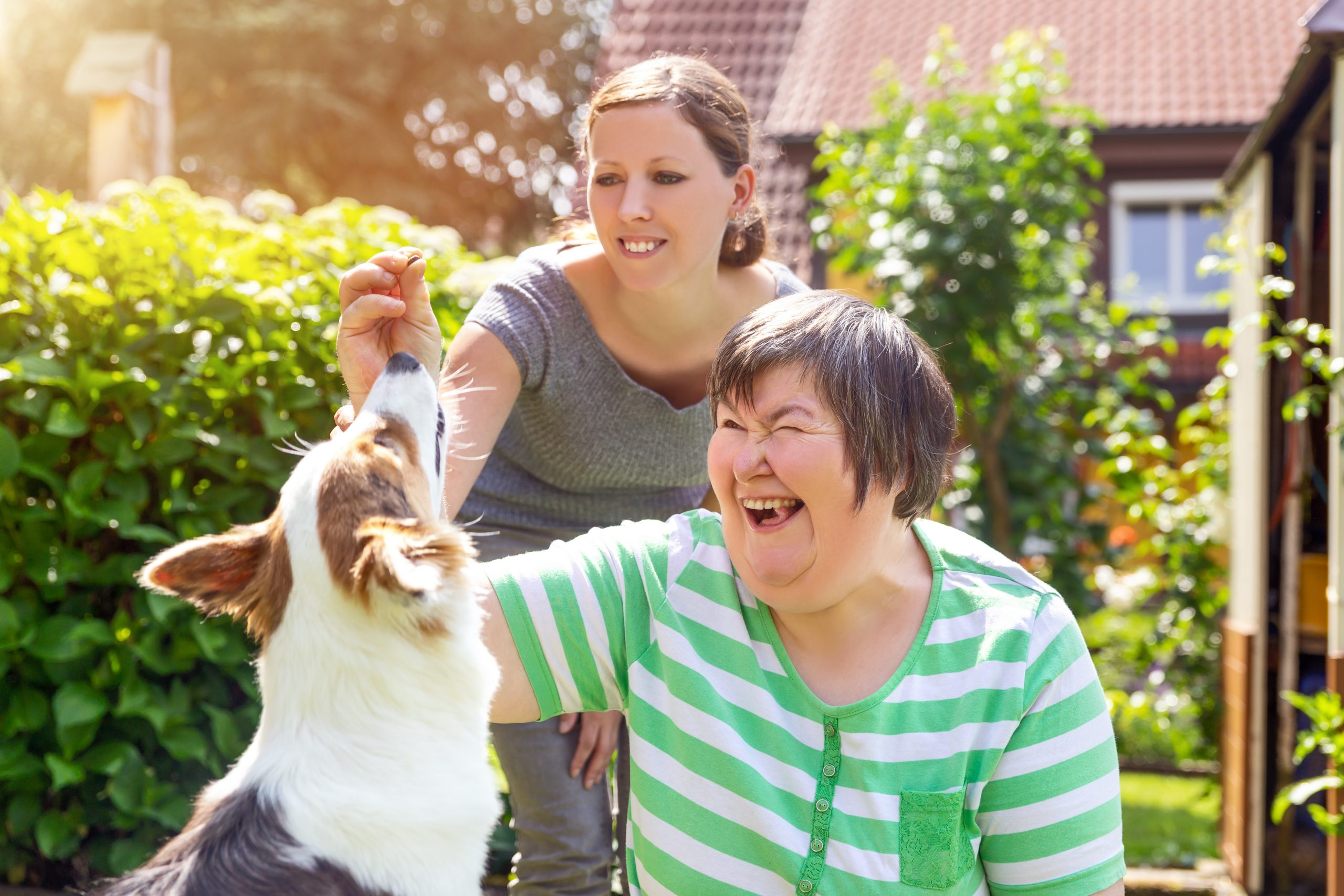 two ladies playing with dog
